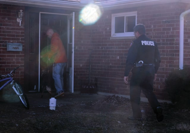 Mike Ullery | Daily Call Tipp City Police Department K9 officer Greg Adkins and his partner Gitta enter a residence on Andover Street in Piqua on Wednesday afternoon, as Piqua Deputy Police Chief Marty Grove allows them room to work, during the service of a drug search warrant at the residence.