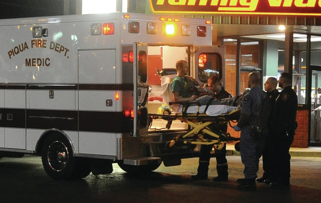 Mike Ullery | Daily Call Piqua Fire Department paramedics and police officers load Tyler Iddings, 28, into a medic unit after medics resuscitated the Covington resident following an alleged drug overdose at the Piqua Family Video store on on Wednesday night.