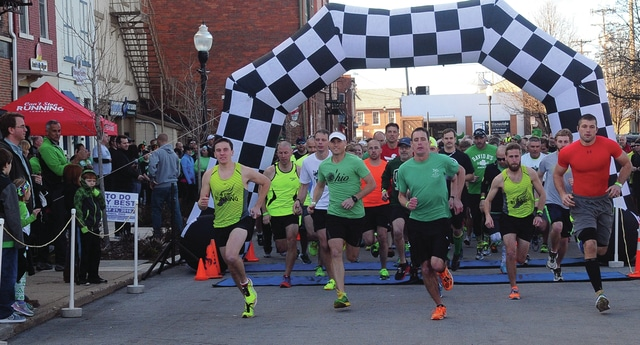 Mike Ullery | Daily Call Runners leave the start line of Piqua's annual St. Patrick Day Beer Run sponsored by Can't Stop Running, 311 Draft House, Mulligan's Pub, and Z's, on Thursday. More than 600 runners ran the 5K course with stops at local pubs to drink a beer, (with options of root beer or water), before returning to the course to complete the race.