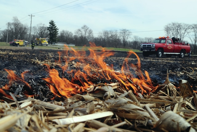 Mike Ullery | Daily Call Firefighters from Piqua, Fletcher, and Casstown battle a field fire in the 1100 block of East Loy Road on Tuesday afternoon. High wind caused the fire to spread quickly and firefighters had to work to keep the fire contained. Approximately 6-8 acres of corn stubble burned before the fire could be extinguished. There were no injuries and no damage to property and a cause of the fire has not been released.