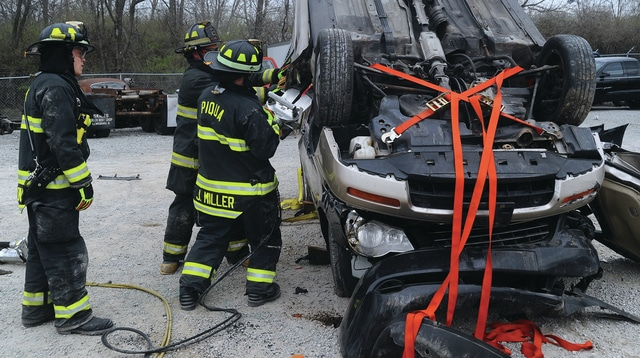 Mike Ullery | Daily Call Piqua firefighters remove the door of an overturned vehicle during a training day on Thursday. Bushnell Collision and Repair donated the vehicles and positioned them to allow firefighters the opportunity to practice on vehicles in precarious situations.