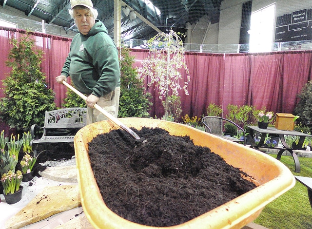 Anthony Weber | Civitas Media Andy Sherick of Greentech Lawn and Irrigation spreads mulch around a display in preparation for the 2016 Miami County Home and Garden Show at Hobart Arena in Troy. According to Sherick, Greentech will offer several seminars on pest control during the event throughout the weekend. Show hours are 2-7 p.m. Friday, 11 a.m. to 7 p.m. Saturday, and 11 a.m. to 4 p.m. Sunday.