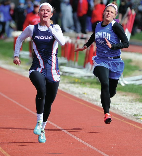 Mike Ullery | Daily Call Piqua's Amy Burt and Miami East's Emma Monnin run in the 100 meter dash event in the Tippecanoe Invitational Saturday.