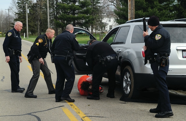 Mike Ullery | Daily Call Troy police and Miami Co. deputies remove a woman from an SUV after a chase where she allegedly attempted to deliberately run down officers with her vehicle on Sunday morning. The chase began in Troy and ended on Piqua-Troy Road near Rusk Road.