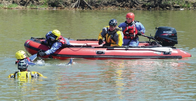 "Mike Ullery | Daily Call Firefighters from Piqua and Sidney train work to get a ""victim"" into a boat during a training exercise on the Great Miami River in Piqua on Tuesday."