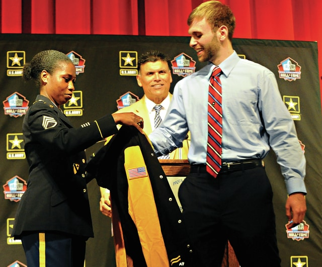 Mike Ullery   Daily Call Pro Football Hall of Famer Anthony Munoz, center, looks on as Piqua High School senior Jack Schmiesing receives a jacket from SSGT Tiffany Smith, United States Army, during ceremonies recognizing Schmiesing as one of 20 finalists in the nation for the prestigious U.S. Army - Pro Football Hall of Fame Award for Excellence, at Piqua High School on Tuesday afternoon.