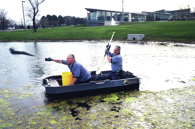 Mike Ullery | Daily Call Edison Community College employees Chuck Whitney and Tom Burelison work from a small boat on Tuesday morning to combat algae build-up at the pond in front near Looney Road.