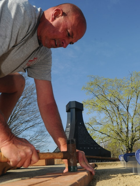 Mike Ullery | Daily Call Long-time area brick mason Tim Kearns, of Support Unlimited, Inc., of Troy, places a brick into a newly-opened section at the Piqua Veteran's Memorial at the corner of St. Rt. 66 and Washington Ave., on Wednesday morning. The project will make an additional 2,200 bricks available to add names of area veterans to the memorial walkway.
