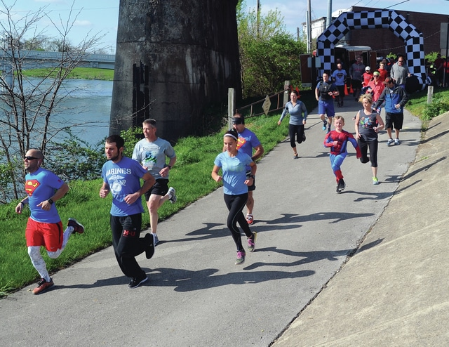 Mike Ullery | Daily Call Runners take to the bike path in Piqua on Saturday morning for the inaugural <em>Superhero Fun Run and 5K</em> at Lock 9 Park. The event drew more than 150 runners to support The Center For Early Learning at St. Patrick School and Piqua Catholic School. Tony Larger of Piqua, far left, won the event with a time of 20:32.