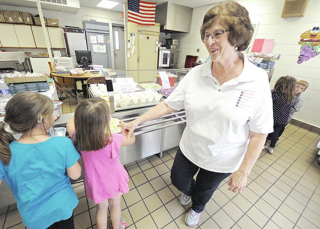 Anthony Weber | Troy Daily News Kyle Elementary School assistant cook Jill Dunfee ensures students, including kindergarteners at the school, get their proper lunch each day at the school.