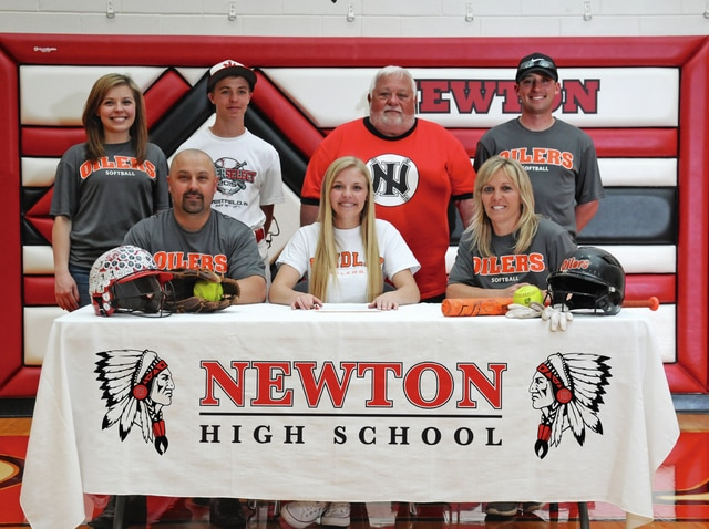 Ben Robinson | GoBuccs.com Newton's Madison Mollette signs her letter of intent to play softball for Findlay University. In front with Mollette are her parents James and Tina Mollette.