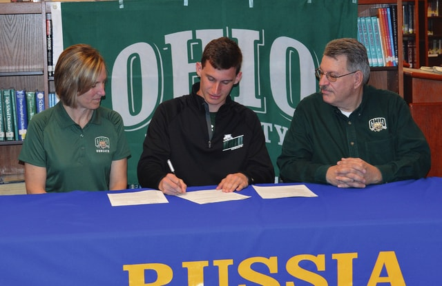 Rob Kiser/Call Photo Caleb Ball signs his letter of intent to run cross country for Ohio University in the Russia High School library Thursday. Looking on are his mother Deanna and father Mark.