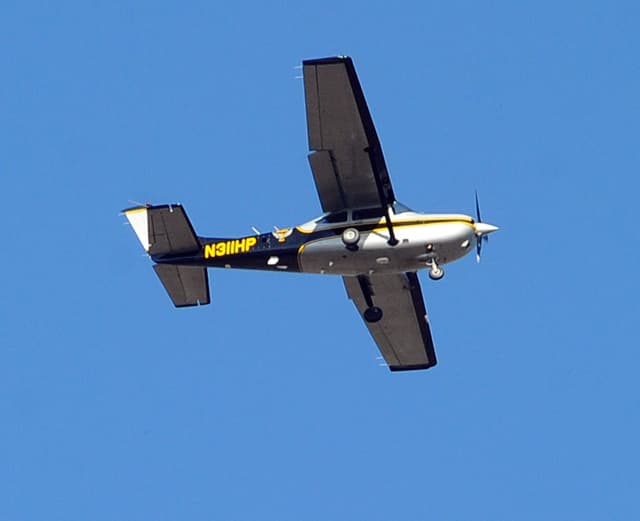 An Ohio State Highway Patrol aircraft circles high over County Road 25-A north of Piqua on Tuesday.