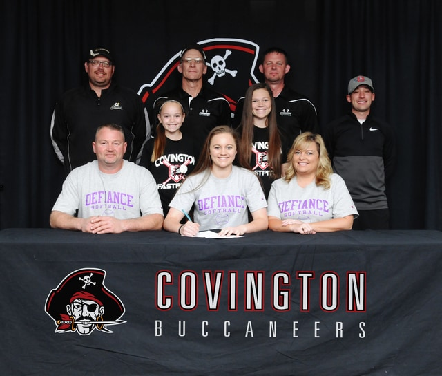 Covington senior Brooke Gostomsky signs her letter of intent to play softball for Defiance College. In front with Gostomsky are her father Brett (left) and mother Susan (right).