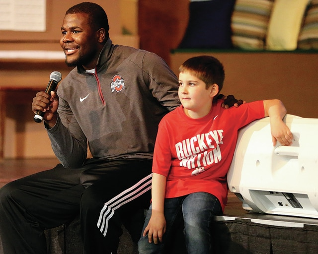 Photo Courtesy of Lee Woolery | Speedshot Photo Former Ohio State quarterback Cardale Jones, left, and Troy Christian kindergarten student Owen Greil meet with Troy Christian students Wednesday during an assembly.