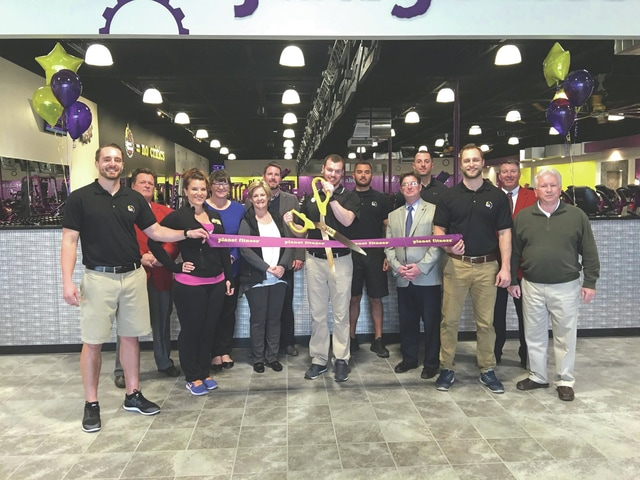 Provided photo Mike McKenna, manager of Planet Fitness, cuts the ribbon at the new business, which opened in late March at 1243 East Ash St., Suite 100, Piqua. Also pictured are Piqua Mayor Kazy Hinds (center, left); Economic Development Director/Assistant City Manager Justin Sommer (behind Hinds); Scott Miller, president of the Piqua Area Chamber of Commerce (center, right); and City Manager Gary Huff (far right); along with PACC Ambassadors and staff of Planet Fitness.