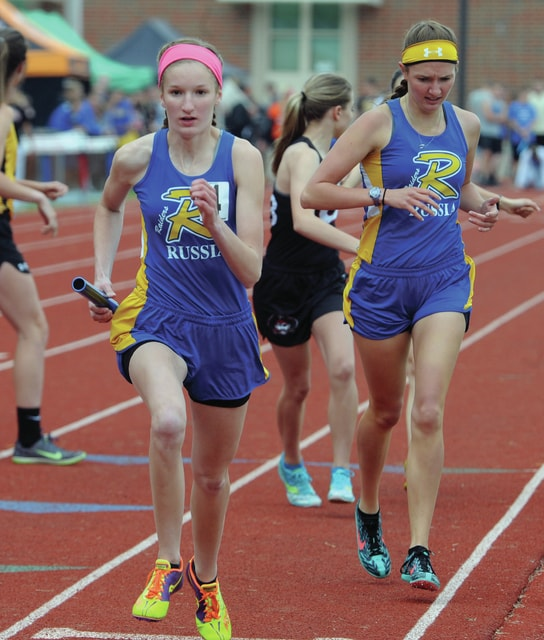 Mike Ullery | Daily Call Grace York, takes the handoff from Shaelyn Goubeaux to start the anchor leg of the 3,200 relay at the Milton-Union D-III district track meet.. The Raider girls took first place in the race to advance to regionals.