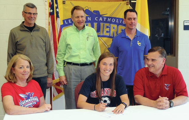 Mike Ullery/Daily Call Lehman Catholic senior Sara Fuller signs her letter of intent to play soccer for Shenandoah University. In front with Fuller are her parents Jeanne and Bill Fuller. In back are club coach Bruce Boyd, former Lehman coach Tony Shroeder and Lehman girls soccer coach Jeremy Lorenzo.