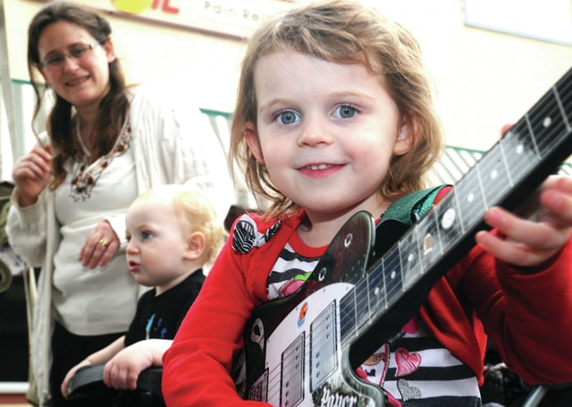 Mike Ullery | Daily Call Jocelien Helton, 3, strums a tune on an electronic guitar in the Music Jam Session booth at Taste of the Arts in downtown Piqua on Friday. The little musician's fans include her brother David, 1, and her mom, Jaci.