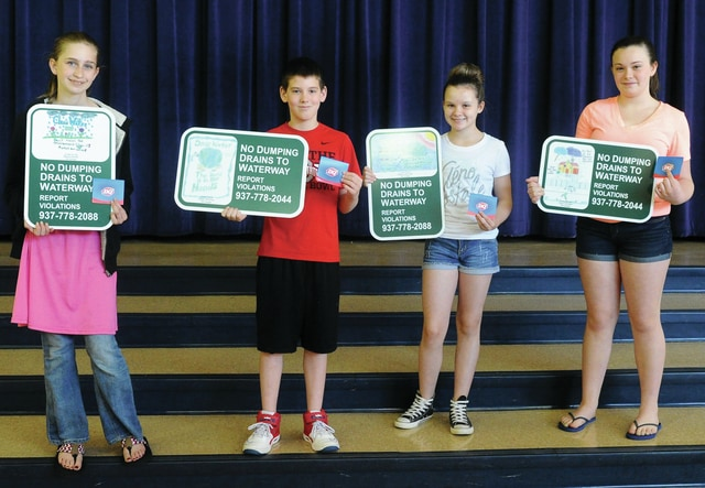 Mike Ullery | Daily Call (Left to right) Seventh graders Alexis Goode, second place; Dylan Wintrow, first place; Adasia Jacomet, fourth place; and Karly Schisler, third place, are the winners of a sign contest with the Piqua Storm Water Department. Their drawings will be featured on signs that discourage pollution and dumping in the Great Miami River and will be placed along the bike path.