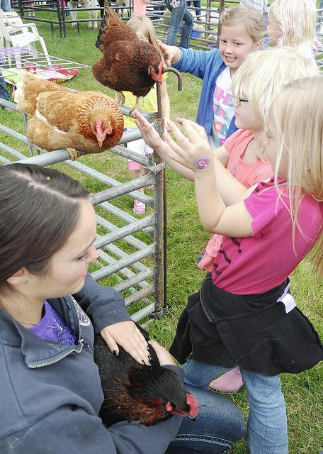 Anthony Weber | Troy Daily News Miami East High School FFA members, including senior Katie Bendickson, help children explore the petting zoo Friday during the school's Ag Day at the Miami County Fairgrounds. Kindergarten and first-grade students of Miami East visited at least nine educational stations throughout the day to learn the story of agriculture, the difference between beef and dairy and the difference in sizes of chickens, ducks and various other farm animals. Earlier in the day, students from Troy elementary schools visited the fairgrounds for Ag Day.