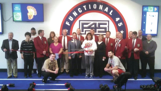 Provided photo F45, a workout/training facility owned by Holly Trombley (holding scissors) and Josh Trombley, celebrated its recent opening in Piqua with a ribbon-cutting attended by Piqua Mayor Kazy Hinds (center right), Piqua Area Chamber of Commerce President Scott Miller (center left), Chamber Ambassadors and F45 staff members. The facility is located in the Riverside Place Plaza strip near the Miami Valley Center Mall.