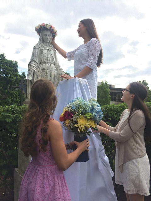Provided photo Diana Gibson crowns Mary as Emma Simpson (right bottom) and Cassidy Hemm (left bottom) bring gifts of flowers to the Holy Mother during the recent May Crowning ceremony held at Lehman Catholic High School.