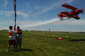 Sean D. Tucker flies under a ribbon, stretched 20 feet above the ground at the 2016 Vectren Dayton Air Show.