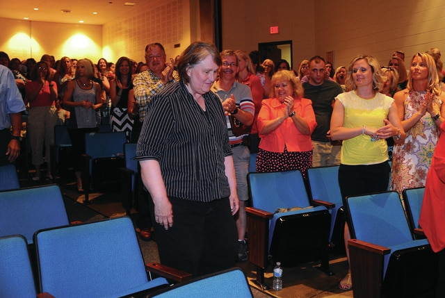 Mike Ullery | Daily Call Brenda Vetter receives a standing ovation as she walks to the podium to receive her retirement gift from Piqua City Schools Superintendent Rick Hanes on Thursday. Vetter retired following 18 years of service as a Music Aide. Joining Vetter were seven other school employees, including Mike Voskuhl who serves the school system as a maintenance employee for 43 years.