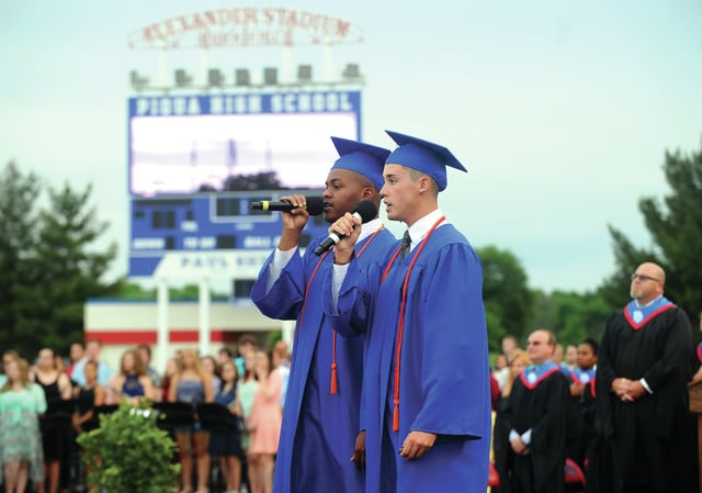 Mike Ullery | Daily Call Class of 2016 seniors Taurean Collier and Troy Iddings perform the National Anthem at the opening of the 153rd Piqua High School Commencement at Alexander Stadium/Purk Field on Friday.