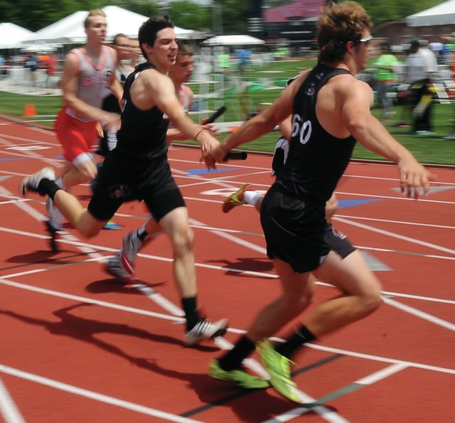 Mike Ullery | Daily Call Covington's Zane Barnes hands off the baton to Brandon Magee in the boys 4x400 meter relay in Columbus on Friday.