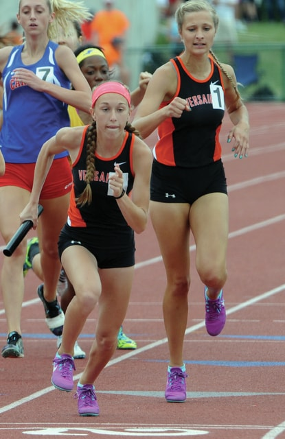 Mike Ullery/Daily Call Versailles' Liz Watren takes a handoff from Emily Langenkamp in the 1,600 relay Saturday.