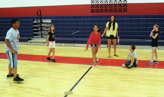 Mike Ullery | Daily Call Madison Doll, center, a Piqua fifth-grader takes her turn at the straw javelin event during Olympics Camp at Piqua Central Intermediate School on Wednesday. Along with Doll, are fellow summer Olympians E.J. Jones, Brenna Thompson, Wesley Thompson, and Julia Thompson and coach Alex Johnson, who teaches sixth-grade social studies at the school.