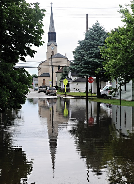Mike Ullery | Daily Call St. Boniface Catholic Church is reflected in high water that flooded the area of Roosevelt and Miami Streets on Friday following heavy rains that moved through the area.