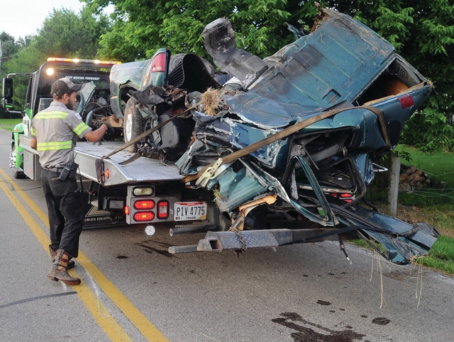 Mike Ullery | Daily Call Workers from Bushnell Collision load the wreckage of a pickup truck onto a flatbed following an early morning crash in the 3000 block of Piqua-Troy Road on Wednesday morning.