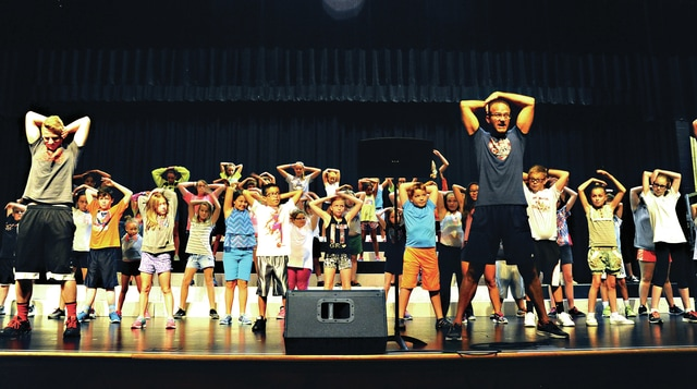 "Mike Ullery | Daily Call Director Tom Westfall, front right, leads a rehearsal at Music Warehouse Boot Camp at Piqua High School on Wednesday. More than 60 area students in grades 3-8 are getting ready for a Friday evening performance of ""Jukebox Time Machine."" The show will begin at 7:30 p.m. in the Hartzell Center for the Performing Arts at the high school."