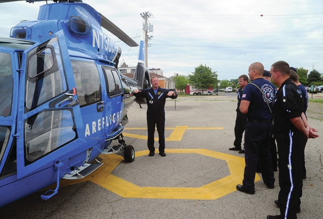 """CareFlight pilot Earl Daniels gives a tour of a CareFlight helicopter to members of the Piqua Fire Department on Wednesday afternoon. Daniels, a U.S. Marine Corps veteran with more than 20 years experience, has been flying for Premier Health/CareFlight for the past five years. Piqua firefighter/paramedics spent a half-day updating their knowledge of working with CareFlight then toured the helicopter, practiced """"hot-loading"""" (loading a patient aboard the helicopter with the engine running and rotors turning just over their heads), along with emergency procedures should the need arise to deal with an emergency aboard the medical rescue helicopter."""
