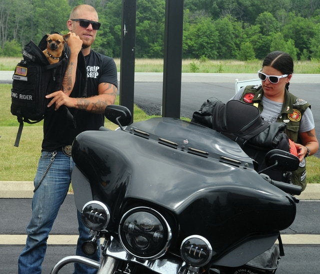 Mike Ullery | Daily Call Adam Sandoval, his dog Scooter, and riding partner Julia Chiriboga, arrive at Piqua Harley-Davidson on Thursday as part of their fund-raising trip for Wounded Warriors that is taking them to every Harley-Davidson dealership in the continental United States.
