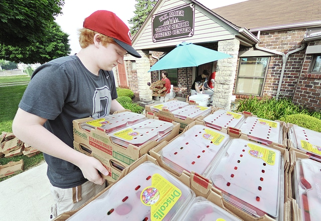 Anthony Weber | Civitas Media Cameron Heffner helps to unload a second delivery of 750 pounds of strawberries that his grandfather, Skip Remy, picked up from Marsh Supermarket Thursday for the Troy Senior Citizens Center in Troy. Members and volunteers were cleaning, washing and slicing the berries in preparation of the center's annual strawberry shortcake sale during the Troy Strawberry Festival this weekend.