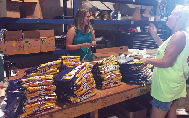Enian Phillips (left) and Sherry Heath (right) folding and packaging printed commemorative Cleveland Cavaliers championship shirts at Atlantis Sportswear in Piqua.