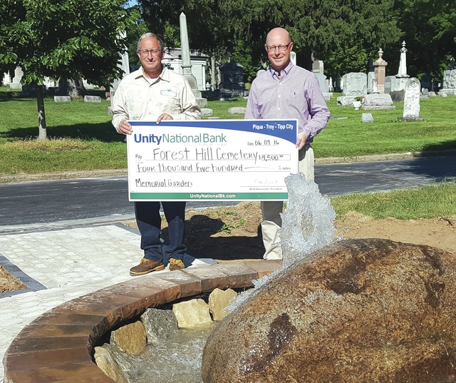 Provided photo Unity National Bank President Brett Baumeister, right, presents Jim Roth, superintendent of Forest Hill Cemetery, with a donation for the creation of a memorial garden at the cemetery. Featuring a center fountain, the garden is currently under construction, following the design of Mark Wion of Casto Landscaping.