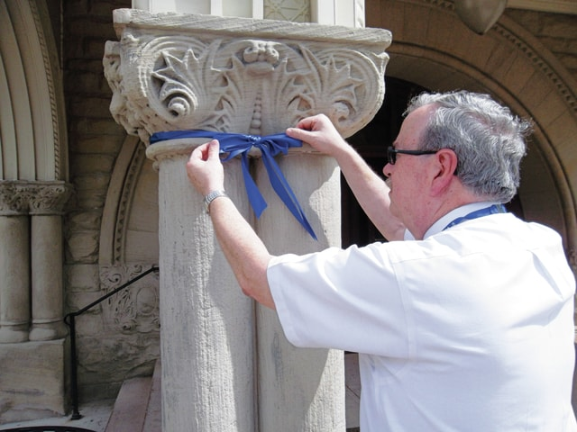 Sharon Semanie | For the Daily Call Piqua Public Library Director Jim Oda encourages residents to tie blue ribbons around trees and/or poles on their properties to show support for Piqua's law enforcement officers.