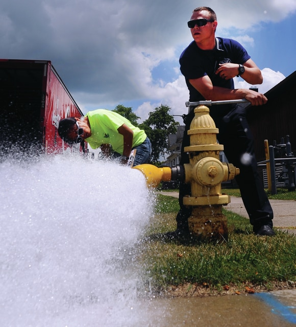 Mike Ullery | Daily Call Piqua firefighter Jon Minton, right, and summer intern Julyia Hsiang test a fire hydrant at the corner of Spring and High Street on Friday. The pair were testing downtown hydrants to update water flow, both PSI and GPM, that each hydrant will produce in the downtown area.