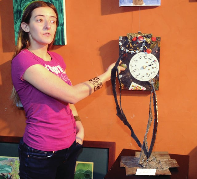 "Mike Ullery | Daily Call Monica Shell of Troy places several pieces of art at the Piqua Arts Council office in Piqua on Wednesday afternoon as part of the Riverside Gallery . Shell, a recent graduate of the Upper Valley Career Center, specializes in creating pieces from ""found art"", using and recycling discarded items to make two and three-dimensional art from plastic and metal. She studied both welding and blacksmithing at the Career Center and has recently been accepted to the Hobart School of Welding where she will continue her education."