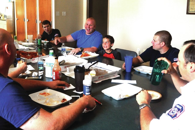 "Mike Ullery | Daily Call Piqua United Way director Sean Ford and his son Spencer, 9, top, sit down to lunch with Piqua Fire Department members on Friday. Ford had the winning bid at last year's Piqua Area Chamber of Commerce Auction on a ""Firefighter for a Day"" that he shared with his son. The day was made extra special for the Fords when they boarded a Piqua fire engine and visited Ford's dad, Robert, who was a member of the Piqua Fire Department from 1966 to 1991."