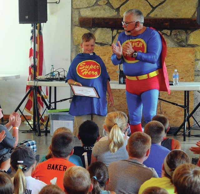 Mike Ullery | Civitas Media Super Hero guest speaker Dave Leedy awards assistant Super Hero status to camp attendee Christian Dohs, of Troy during Miami County Sheriff's Office 2016 Youth Camp at the Redmen's Campground on Wednesday.