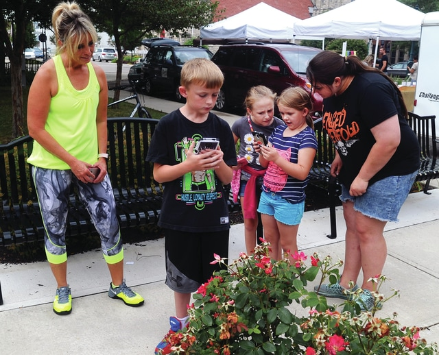 Mike Ullery | Daily Call Jayce Johnson, 8, Alyssa Brock, 11, and Kaylianna Rudy, 5, search for Pokemon characters in downtown Piqua on Thursday, with some assistance from Joely Rudy and Jalisha Rudy.