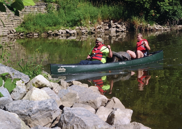 Mike Ullery | Daily Call Renee Ford and Jacob Hawkins, of Troy, nose in to Twin Arch Reserve with a canoe load of old tires and other assorted items of trash during Friday's Great Miami River Cleanup.