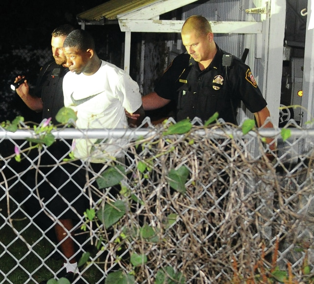 Mike Ullery | Daily Call Lt. Bill Weaver and Officer Jeremy Weber lead suspect Antonio Williams from a garage behind a South Downing St. residence after capturing Williams inside the garage early Sunday morning.