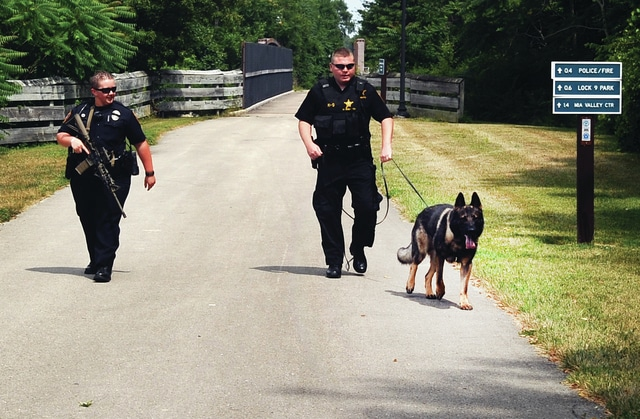 Mike Ullery | Daily Call Piqua officer Mallory Lash, Miami County Deputy Will Roberts, and K-9 Bear search the bike path near French Park following a report of shots fired at a subject on Thursday afternoon.